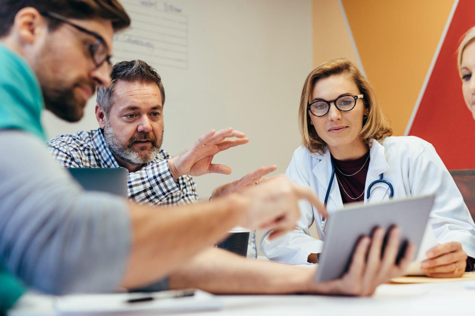 ryhmä terveydenhuollon työntekijöitä lääkärin kanssa kokouksessa. Istuvat pöydän ääressä ja katselevat tabletilta jotakin.