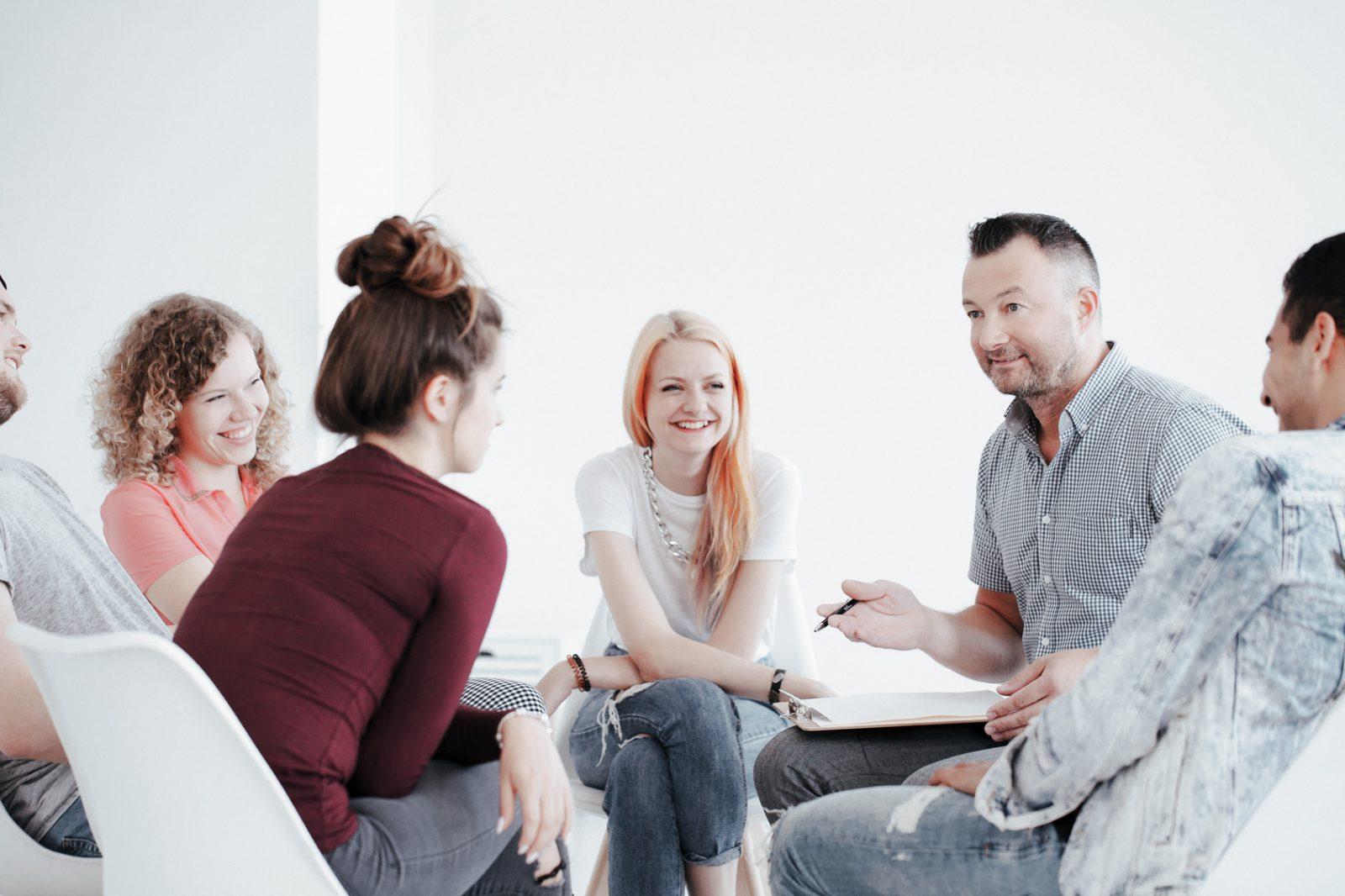 ryhmä nuoria henkilöitä kuuntelemassa ja keskustelemassa kokemustoimijan kanssa istuen ympyränmuotoisessa piirissä